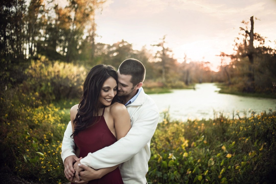 couple holding each other and touching faces during outdoor engagement photo shoot session