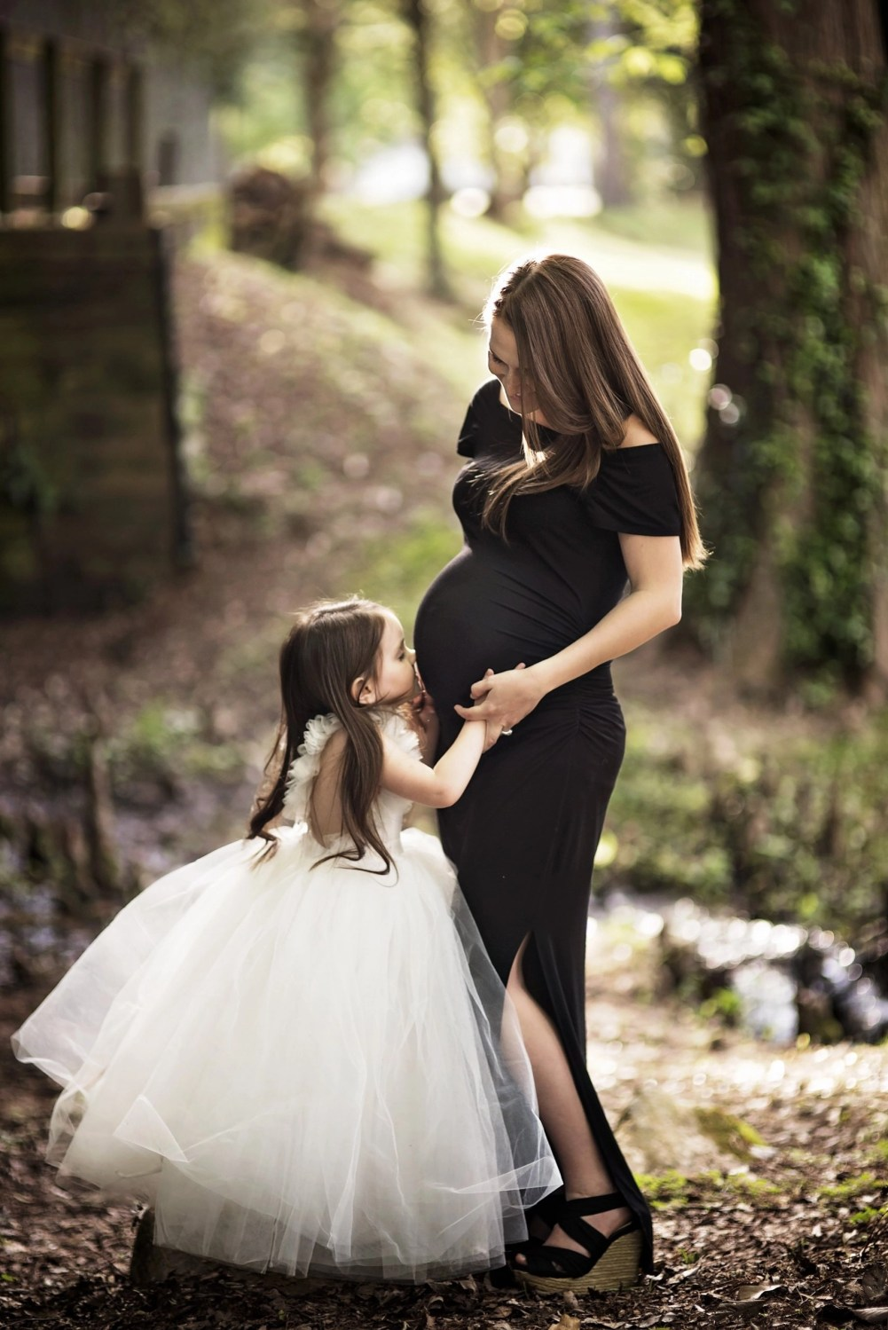 maternity photograph of daughter kissing baby bump