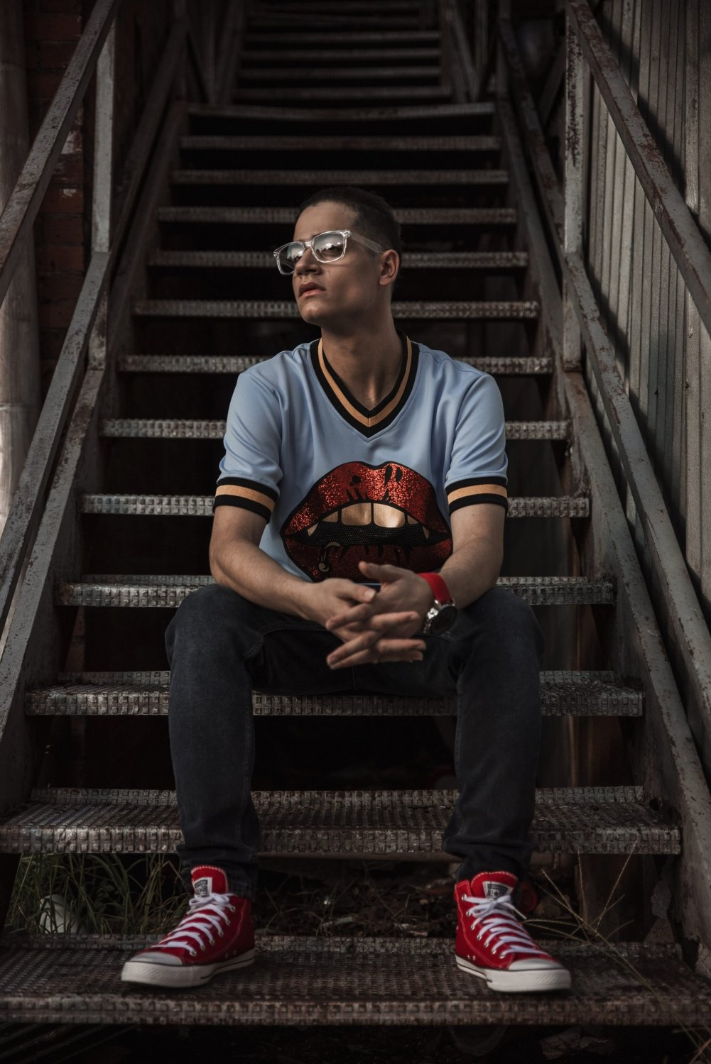 creative senior photograph of male sitting on stairs wearing glasses red converse
