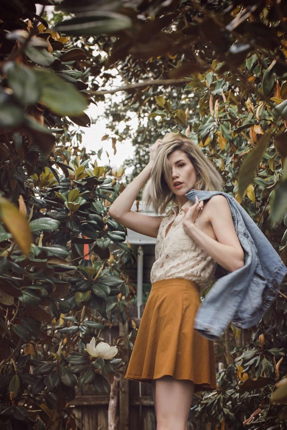 blonde senior holding hair in leaves mustard skirt denim jacket