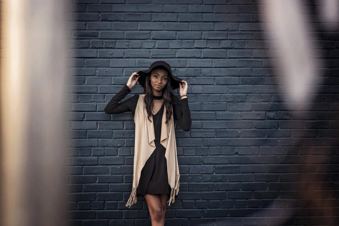 senior photo against brick in boho dress kimono hat