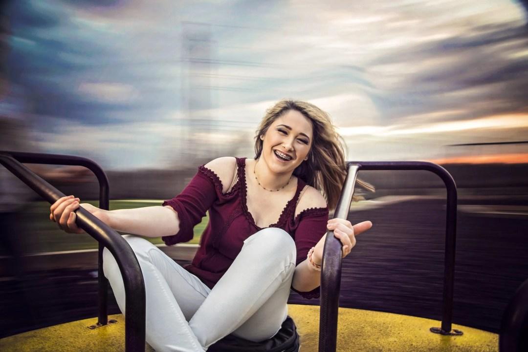 fun senior portrait smiling on merry go round