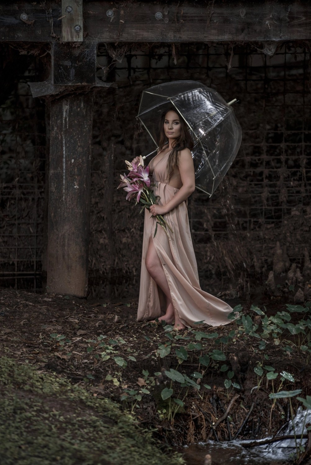 brunette in pink dress holding umbrella and flowers senior photography session