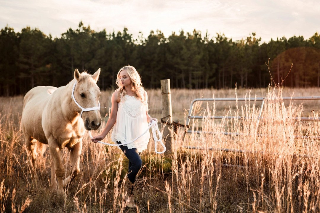 blonde senior in field with her horse