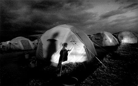 Shadows of children dance across a small tent city - temporary shelter for homeless families - in Cabaret