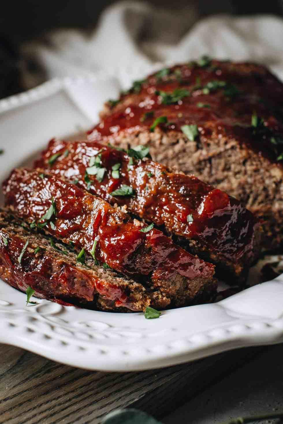 Image of sliced meatloaf on white platter