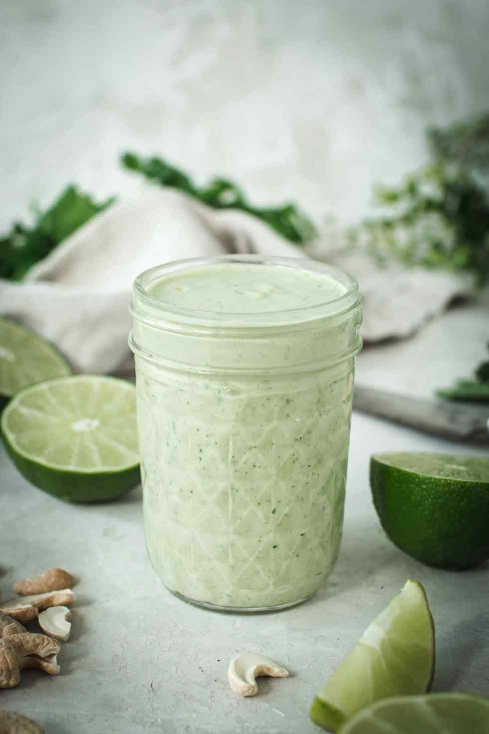 dairy-free vegan lime crema in glass jar with cashews and lime halves surrounding