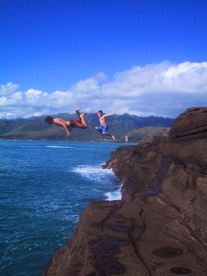 Two guys cliff jumping in beautiful Hawaii weather.