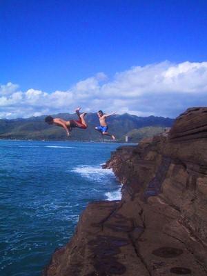 Two guys cliff jumping in beautiful Hawaii weather.