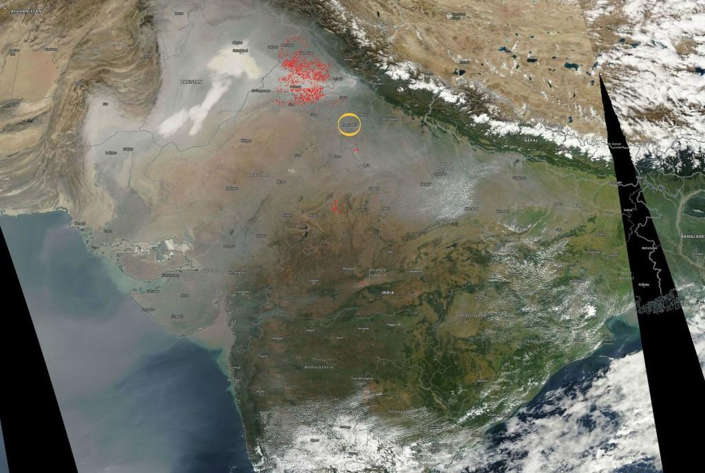 Sur cette image de la NASA, on peut apercevoir le « smog » de l'espace par un voile grisé. En rouge les brûlis agricoles et en jaune, la ville de New Delhi.