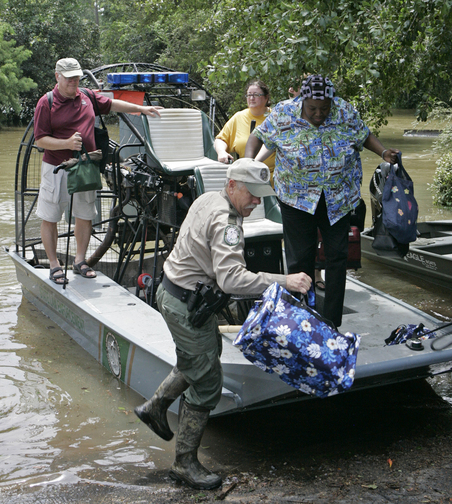 Algussie Thompson is helped ashore by Fish and Wildlife officer Charles Higman after Tropical Storm Fay flooded her Timber Lake neighborhood on Sunday, Aug. 24, 2008 in Tallahassee, Fla. photo: AP/Steve Cannon