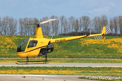PH-SEW Robinson R22 Beta II met een perfecte schutkleur tussen de paardenbloemen