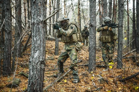 Norwegian Rapid reaction special forces FSK soldiers in field uniforms patrolling in the forest trees