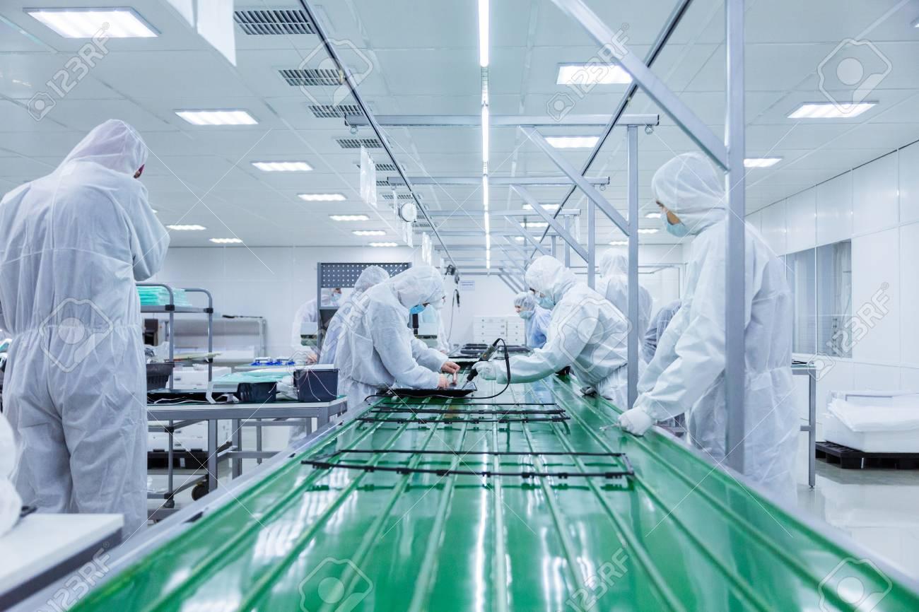 90860453 operai in abiti da laboratorio bianchi e maschere facciali producendo televisori su una catena di mo Avvitatori per assemblaggio industriale