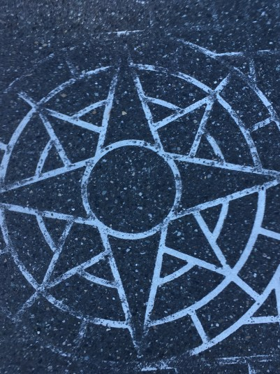 Crosswalk pattern on pavement in Bellingham, white brick pattern with a compass rose
