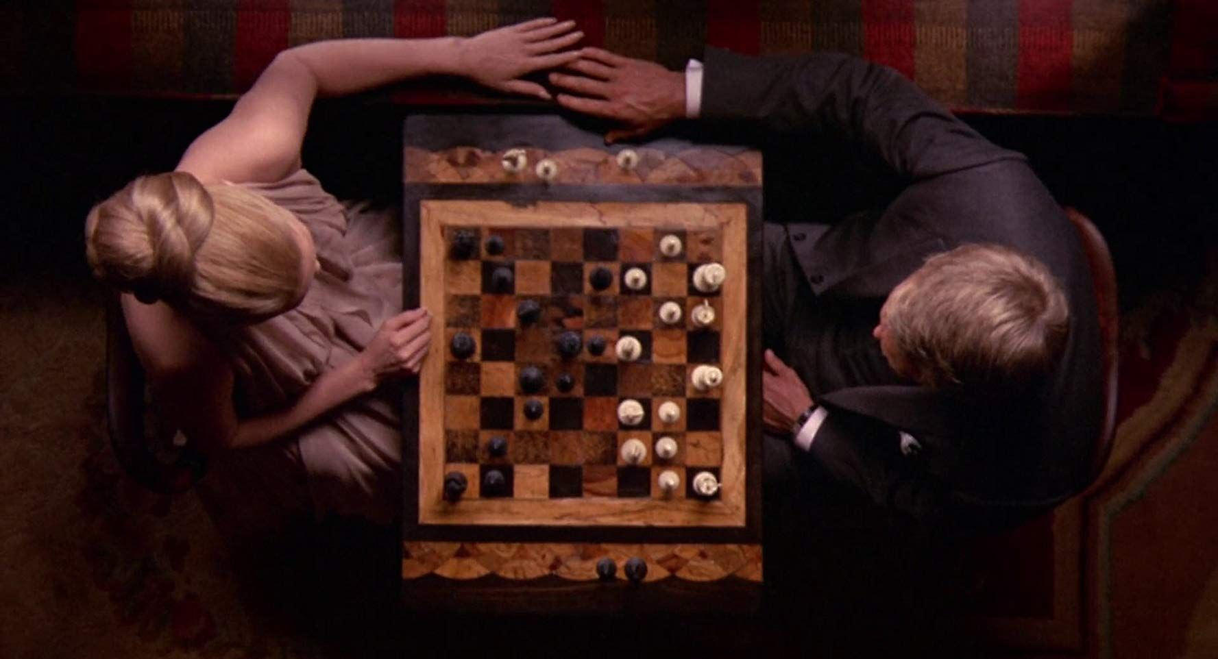 Top down shot of McQueen and Dunaway playing chess from the film