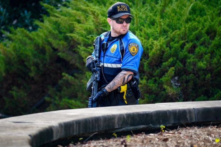 A KSU police officer stands watch outside the Austin Residence Complex