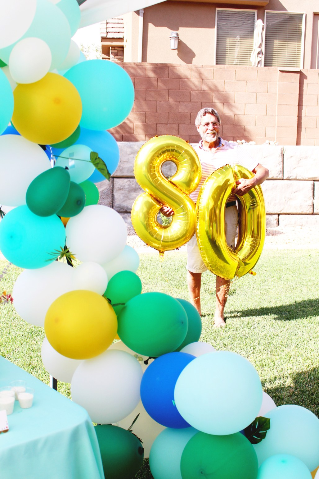 green, blue, turquoise, white, gold balloon arch with number balloons