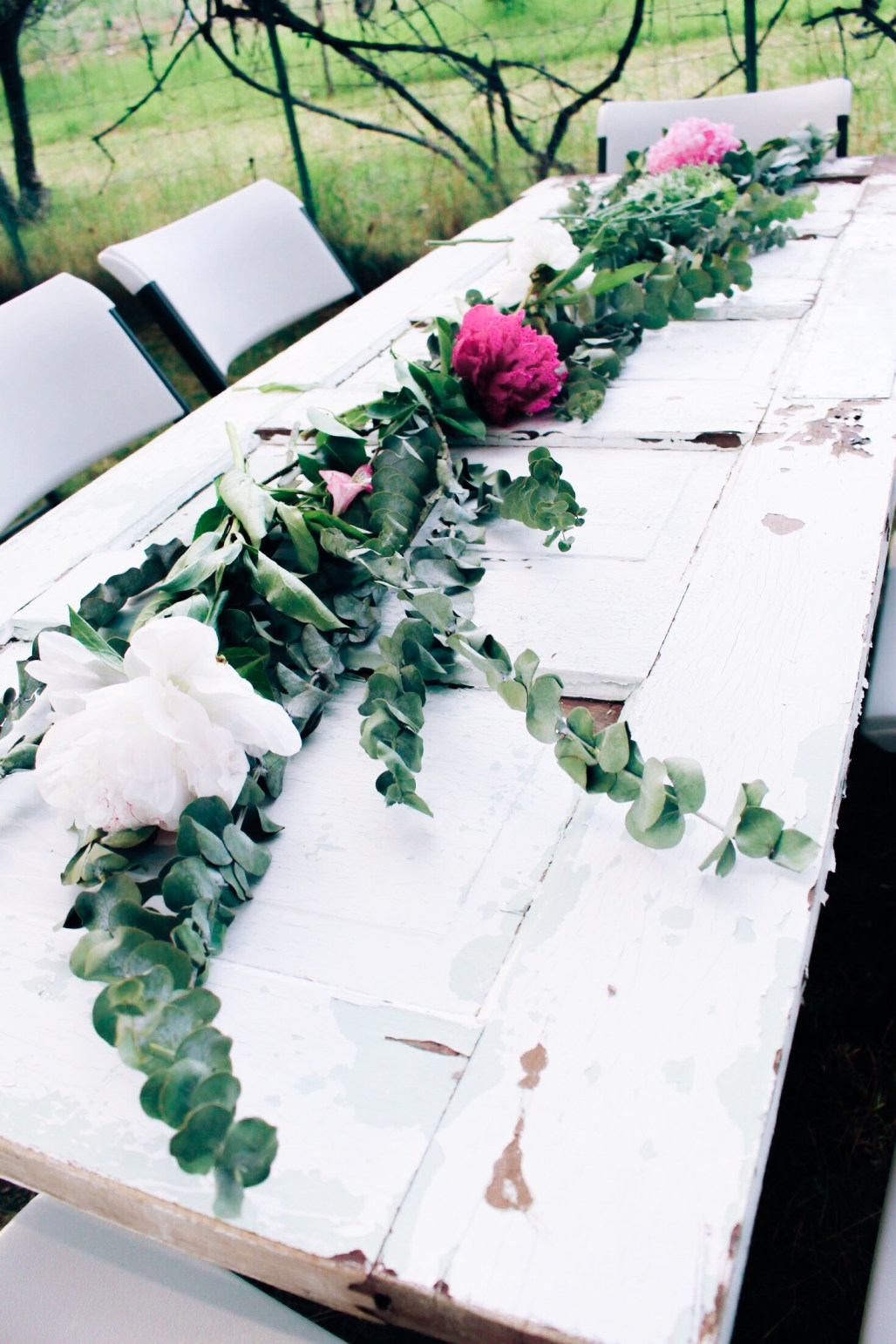 Vintage door made into a table with a eucalyptus and peonie centerpiece at a pink and rose gold bridal shower