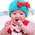 cute baby with a cyan colored bonnet