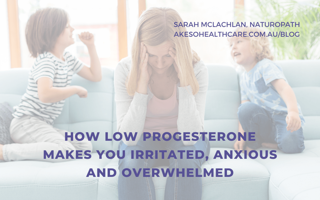 How Low Progesterone Makes You Feel Irritated, Anxious and Overwhelmed - Sarah Mclachan Naturopath - woman holds her head while sitting on a couch. Two children sit on either side of her.