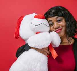 woman holding white bear plush toy