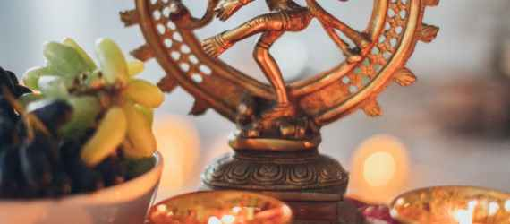 shiva nataraja figurine surrounded by lighted tealights
