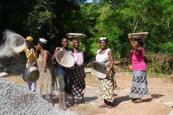 Frauen bringen Steine den Hügel hinauf zur Baustelle