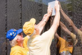 A veteran from the Tuscaloosa traces a friend's name. (Simo Ahmadi/Alabama NewsCenter)