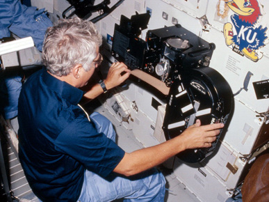 Astronaut Henry Hartsfield (1933-2014) loads film into the IMAX camera on board the Space Shuttle Discovery during the August 1984 mission. (From Encyclopedia of Alabama, photo courtesy of NASA)