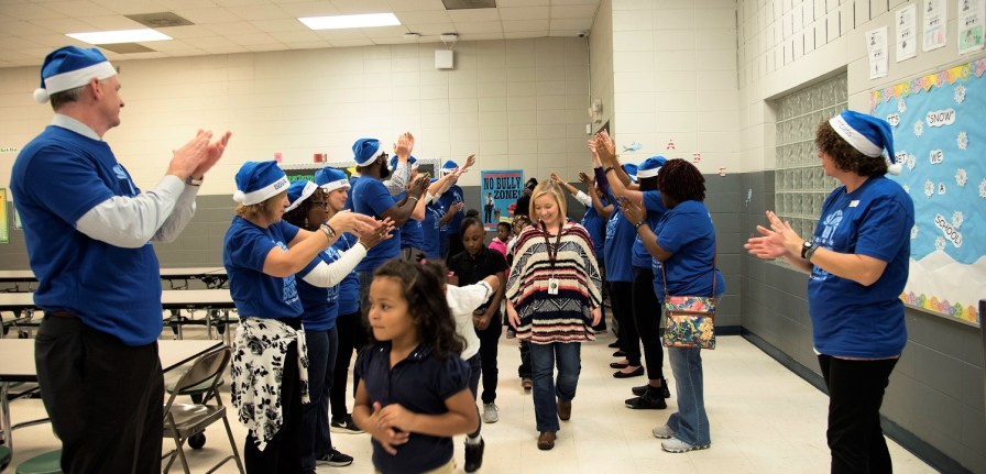 """The """"blue elves"""" of BBVA Compass greet the children of South Hampton K-8 for some holiday fun. (Brittany Faush / Alabama NewsCenter)"""