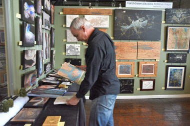 David Nuttall at work in his Huntsville studio. It always surprises him when other people buy into his imaginary places, he says. (Karim Shamsi-Basha / Alabama NewsCenter)