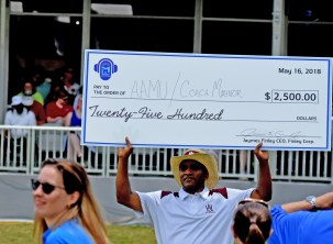Alabama A&M Coach Connell Maynor displays the scholarship check he earned by besting Alabama State's Donald Hill-Eley at the Regions Tradition Pro Am. (Solomon Crenshaw/Alabama NewsCenter)