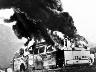The burning Greyhound bus pictured here carried Freedom Riders into Anniston on May 14, 1961, as part of an effort to test a newly enacted integration law regarding bus stations in the South. After the riders were attacked at the station in Anniston, the bus was firebombed after breaking down several miles outside the city. Many of the riders were beaten, with several being severely injured, by a white mob as they departed the bus. (From Encyclopedia of Alabama, Birmingham Public Library Archives)