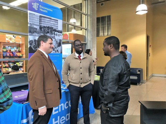 Amartei Amamoo, a senior at Miles College, speaks with representatives from Encompass Health during the Code the Classic Tech Expo. (Erica Wright/The Birmingham Times)