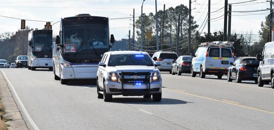 Buses carrying Thompson football players get a police escort. (Solomon Crenshaw Jr./Alabama NewsCenter)