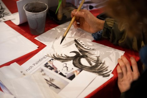An attendee at the Birmingham Museum of Art's Japanese Heritage Festival works at Asian brush painting. (Phil Free/Alabama NewsCenter)