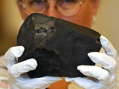 Rosa Hall, of the Alabama Museum of Natural History, displays a fragment of the Hodges meteorite. The meteorite struck Sylacauga resident Ann E. Hodges on the leg when it crashed through the roof of her house in 1954. (From Encyclopedia of Alabama, photograph by Charles Nesbitt, courtesy of The Birmingham News)