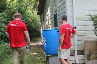 Volunteers from the Alabama Power Service Organization help install rain barrels at a home in Prichard. (Beth Thomas / Alabama Power)