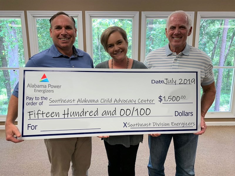 Scott Applefield (left), past president of the board - Southeast Alabama Child Advocacy Center, with Executive Director Terri Dubose, were thankful for the generous gift from Southeast Energizers, represented by chapter President Ken Lane (right). (Southeast Energizers)