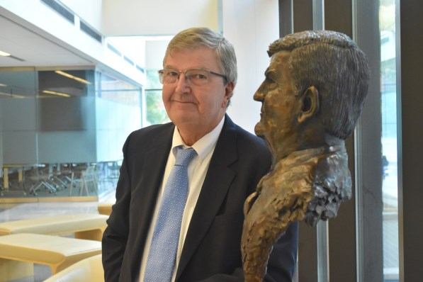 Dr. Edward Partridge stands next to his likeness in the O'Neal Comprehensive Cancer Center at UAB. For the past 25 years, Partridge has been working to reduce disparities in cancer outcomes in Alabama's Black Belt, with remarkable results. (Karim Shamsi-Basha/Alabama NewsCenter)
