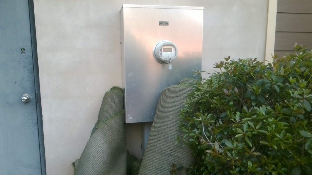 Both shrubbery and carpet rolls block access to an electric meter. Alabama Power field specialists often encounter such obstacles when doing their jobs. (contributed)