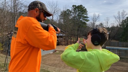 Jeff Carter (left) shows Drake Arden how to shoot a shotgun. (Dennis Washington / Alabama NewsCenter)