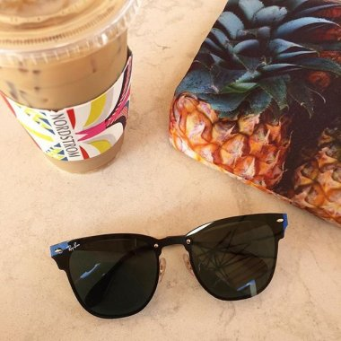 Ray Ban sunglasses, a cup of ice coffee and a pineapple.