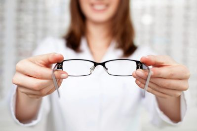 Woman holding eyeglasses with her two hands