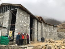 """This is the KCC building with the three volunteers, Jenni and Tenzing (local electrician). It's a """"hati"""" strength structure. Exterior top rope wall. There are three of with built in steel anchors at the top."""