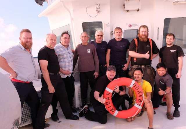 Besättningen på M/S Midas tillsammans med de tre personerna som räddades. Foto: Kalle Lehtinen