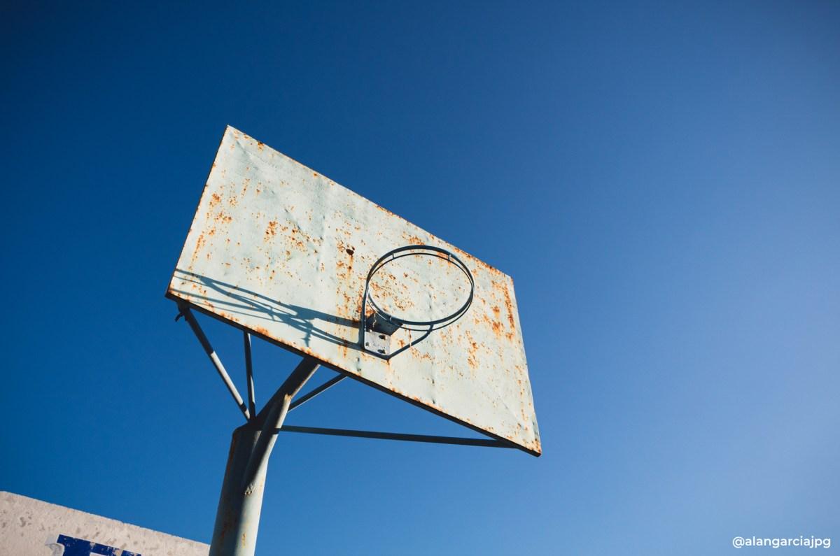 Vieja y oxidada canasta de baloncesto con un cielo azul.
