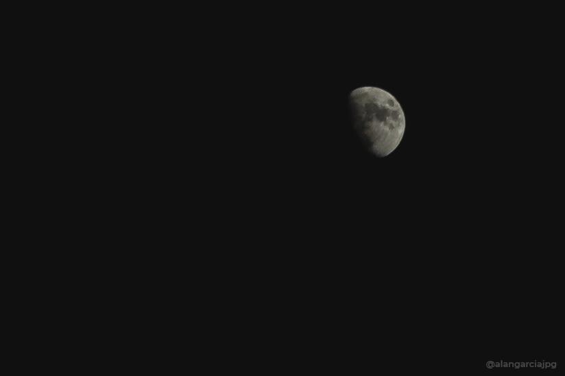 Luna creciente en cielo nocturno despejado.