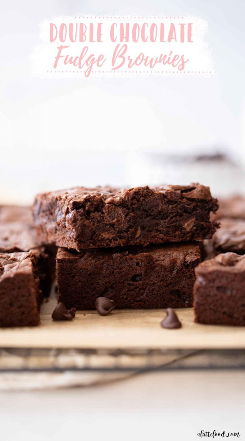 stack of fudge brownies with chocolate chips on brown parchment paper